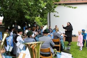 Voller Schwung und von Kindern umringt dirigiert Schwester Regina die Blaskapelle